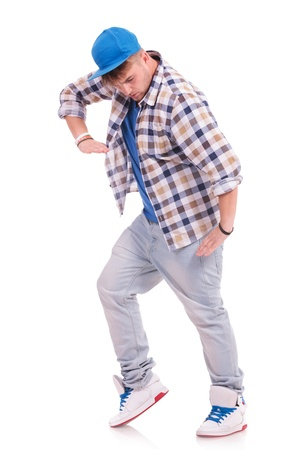 cool young casual man in dance pose looking down, on white photo