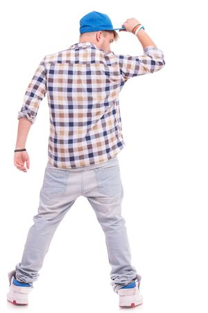 back view of a cool young casual man with his hand on his cap. isolated on white  photo
