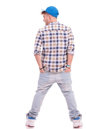 Handsome young casual man from back, looking to his side. Hands in pockets. Studio shot. White background. photo