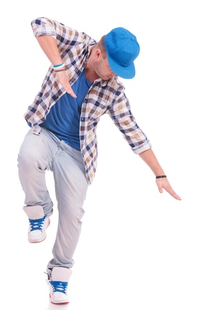 young dancer standing on one leg in a dance position with hands and look pointing down, isolated on white photo