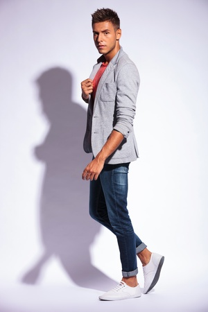 suspiciously: full length side view picture of a casual young man looking suspiciously at the camera while holding his jacket, on a light background with shadow