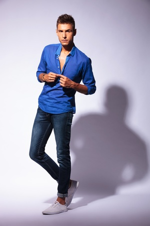 shirt unbuttoned: full length picture of an attractive young man unbuttoning his shirt and looking at the camera, on light background with hard shadow