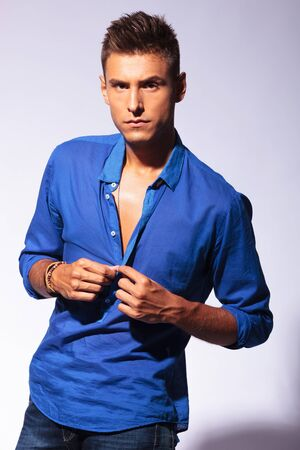 unbuttoned: closeup picture of a sexy young man unbuttoning his blue shirt, revealing a beautifully tanned skin, looking at the camera, with serious attitude, on light background