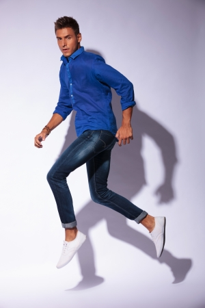 casual young man jumping in a walking position and looking at the camera, on light background with shadow photo