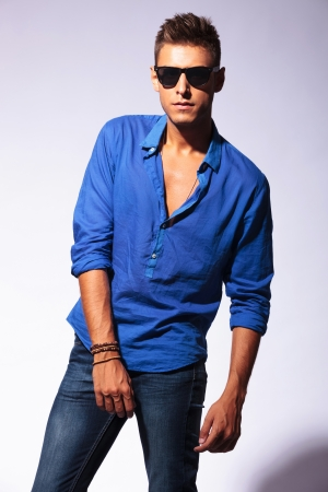 shades of grey: portrait of a casual fashion young man wearing sunglasses posing serious on a light background