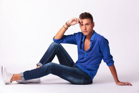 male fashion model: full length picture of a casual young man sitting on the floor and looking pensively at the camera, on gray background