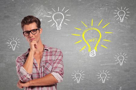 got: Young Man with glasses Having many Ideas. Light bulbs around him Stock Photo