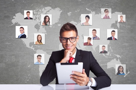Collage with a smiling business man with tablet pad  against technology background, communicating with entire world photo