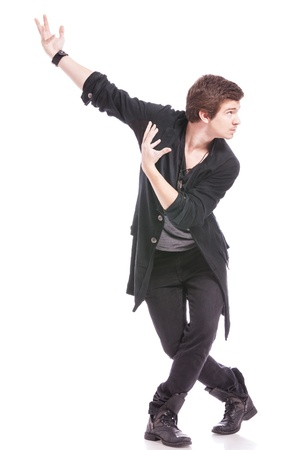 dance pose: young male dancer in a cross legged pose, looking to his side, away from the camera