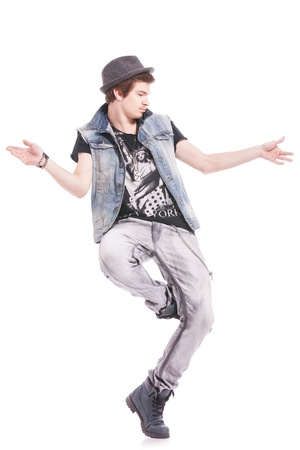 young male dancer showing his skills, posing in one leg and arms apart, looking away from the camera photo