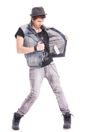 dance pose: young casual man taking of his jeans vest while looking away from the camera Stock Photo