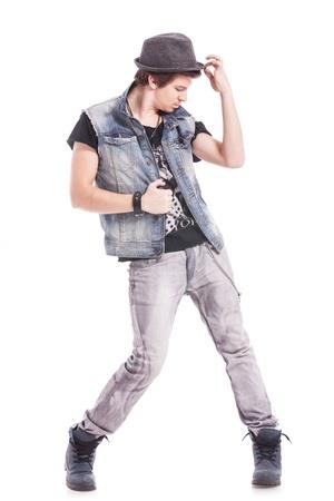 danza contemporanea: imagen de cuerpo entero de un joven bailarín masculino que sostiene el chaleco y el sombrero mientras mira hacia abajo y hacia un lado