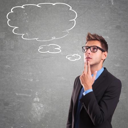percepción: Hombre de negocios joven con las burbujas del discurso adentro. Pensando en el hombre. Imagen conceptual de un man.On mente abierta un fondo gris