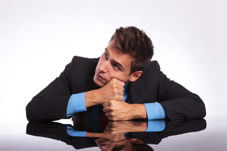 young pensive business man sitting at the desk with his fists supporting his head and looking away photo