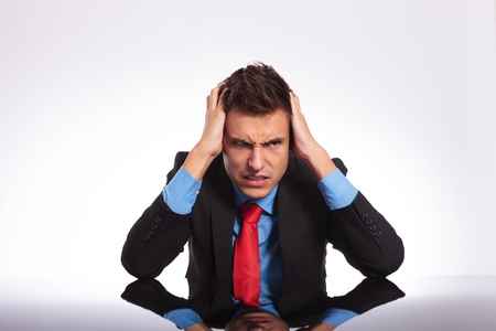 despaired: young business man sitting at his desk and looking despaired away from the camera with a mad look on his face