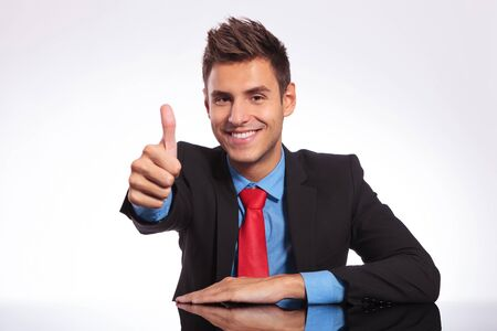 young business man at the table and showing thumbs up sign with a smile on his face while looking at the camera Stock Photo - 18025316