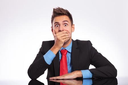 hombre sentado: joven hombre de negocios sentado en la oficina y mirando sorprendido a la c�mara que cubre la boca con la mano