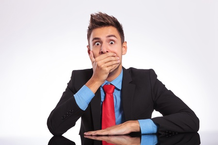 young business man sitting at the office and looking shocked at the camera covering his mouth with his hand photo