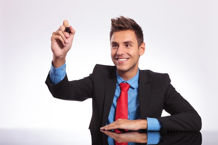 young business man sitting at the desk and writing something on an imaginary screen while smiling Stock Photo - 18025303