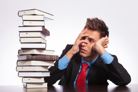 pile of books: young business man slaping himself while seeing the stack of books he has to read