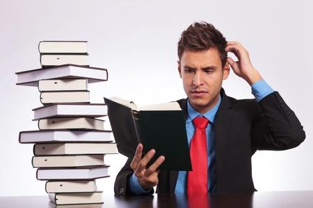 confundido: hombre de negocios joven confundido de lo que est� leyendo en su escritorio Foto de archivo
