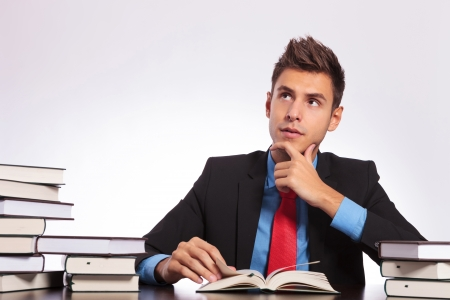 young business man sitting at the desk and reading with a contemplative look on his face Stock Photo - 18025274