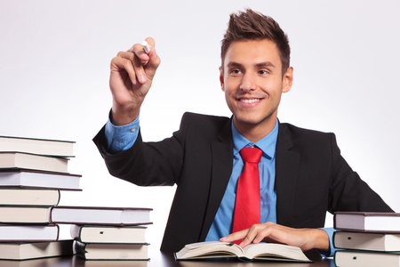 young business man sitting at his desk full of books and writing something with chalk on an imaginary screen Stock Photo - 18025270