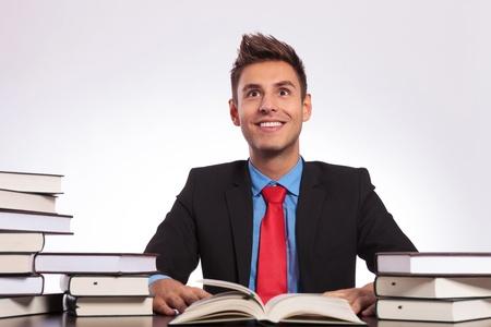 struck: young business man sitting between books struck by an idea Stock Photo