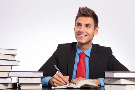 young business man at a desk full of books, thinking while witing with a smile on his face photo