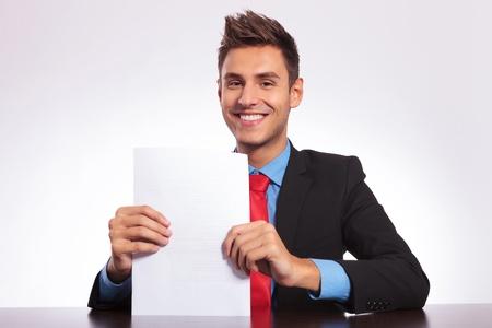 hombre sentado: joven hombre de negocios sentado en el escritorio y la celebración  presentar un montón de papeles, mientras sonriendo a la cámara Foto de archivo