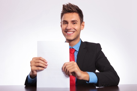 seated: young business man sitting at the desk and holding  presenting a bunch of papers while smiling at the camera Stock Photo
