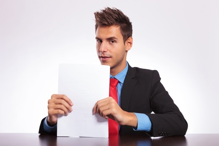 young business man at the table holding some papers and looking into the camera photo