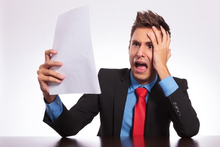 young business man at his desk stunned by something he is reading on some paper sheets Stock Photo - 18025390