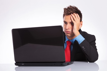 too much work: young business man sitting at desk is overwhelmed of too much work on his laptop Stock Photo