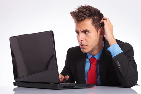 baffled: young business man sitting at the desk and looking baffled at his laptop