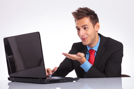 young business man sitting at the desk and sending kisses to his sweetheart through the laptop Stock Photo - 18025271