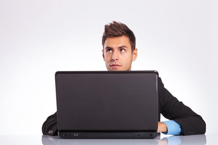young business man sitting at the desk on his laptop and thinking photo
