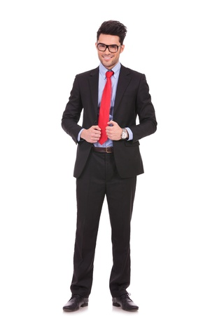 both: full length picture of a young business man holding his suit jacket with both hands and smiling to the camera on white background Stock Photo