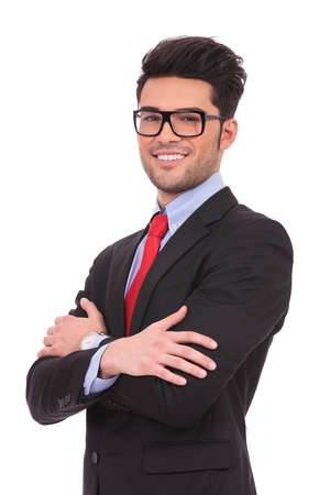 angle view of a young business man standing with his hands crossed and looking at the camera with a smile on his face, over white background photo