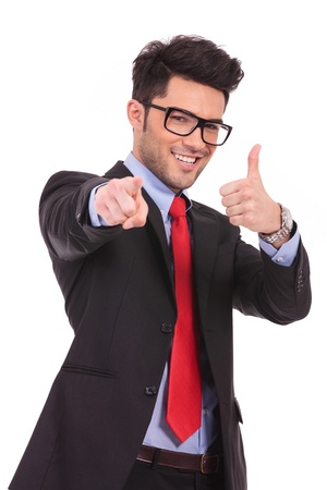 young business man pointing towards the camera and showing thumbs up sign, on a white background photo