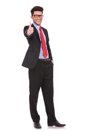 politician: full length picture of a young business man showing thumb up and holding the other hand in his pocket, while smiling to the camera  on white background
