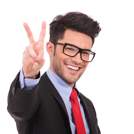 victory stand: closeup of a young business man showing victory sign on white background Stock Photo