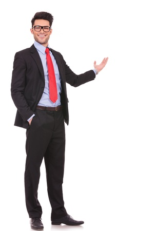 indicating: full length picture of a young business man presenting something in the back with one hand in his pocket while looking at the camera with a smile on his face, on white background