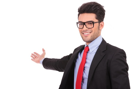 indicating: closeup picture of an attractive young business man presenting something in the back while looking at the camera and smiling, on a white background