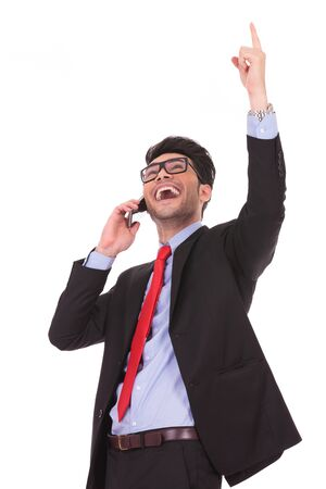 portrait of a young business man talking on the phone and pointing upwards, while looking away from the camera and laughing on a white background photo