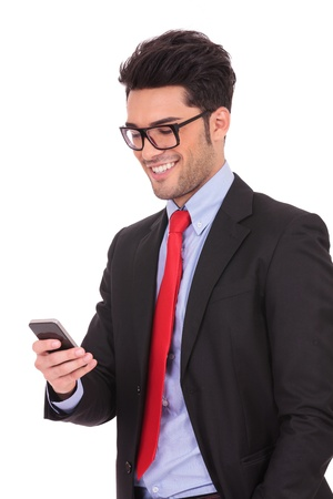 closeup portrait of a young business man standing with a hand in his pocket and texting on his phone, on a white background photo