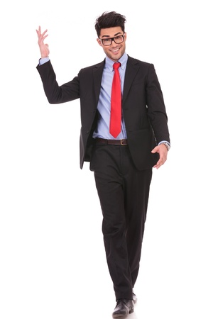 full length picture of a young business man walking forward with one of his hands in the air and smiling to the camera on white background photo