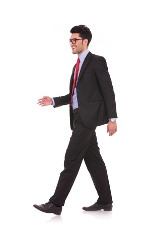 looking away from camera: side view full length picture of a young business man walking and looking away from the camera on white background Stock Photo