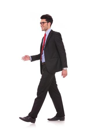 zijaanzicht volledige lengte foto van een jonge zaken man lopen en kijken weg van de camera op een witte achtergrond Stockfoto