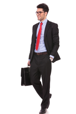 full length picture of a young business man walking forward with a briefcase and holding a hand in his pocket, while looking away from the camera on white background